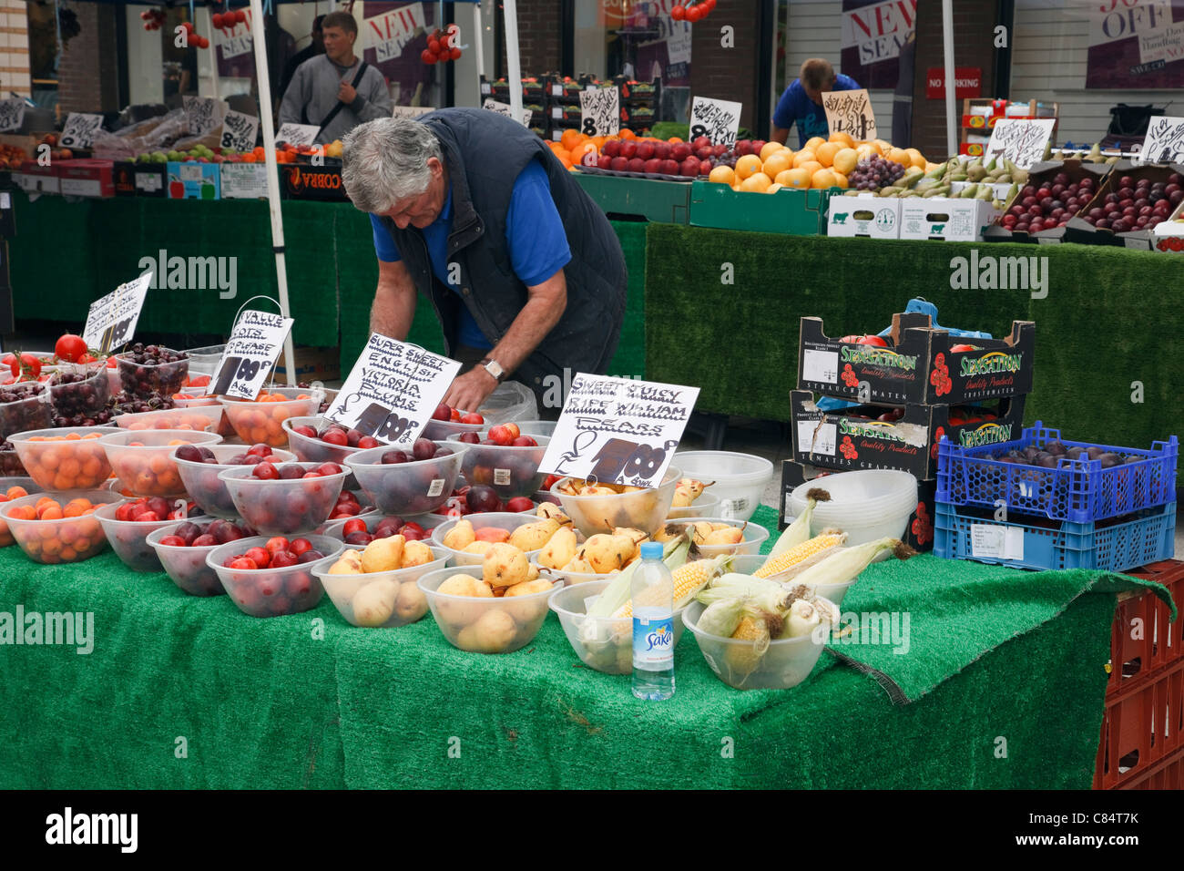 England, UK, Britain, Europe. Man selling bowls of fruit on a market stall - Stock Image
