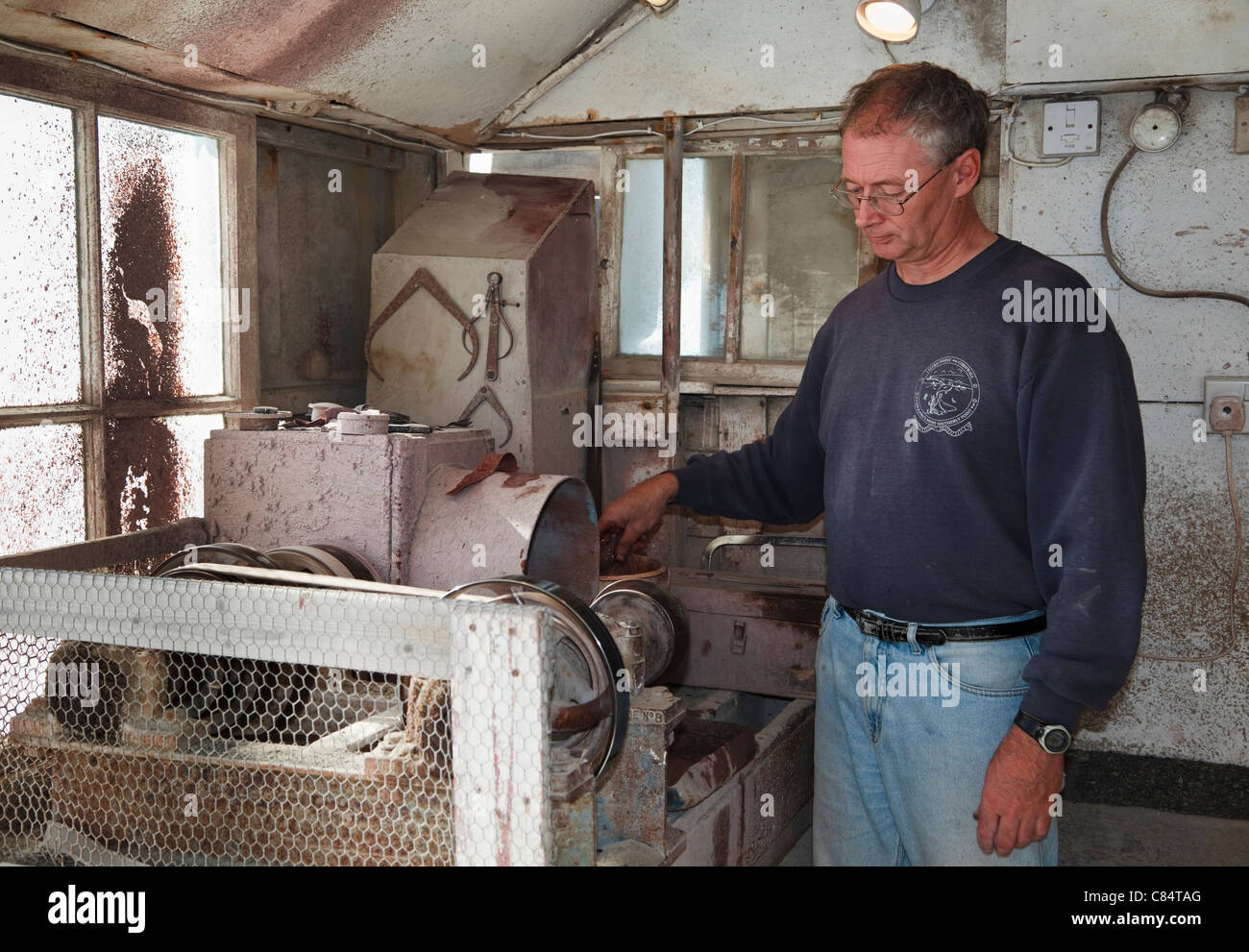 Local craftsman Ian Casley hand turning serpentine stone on machinery in his workshop. Lizard Point Cornwall England - Stock Image
