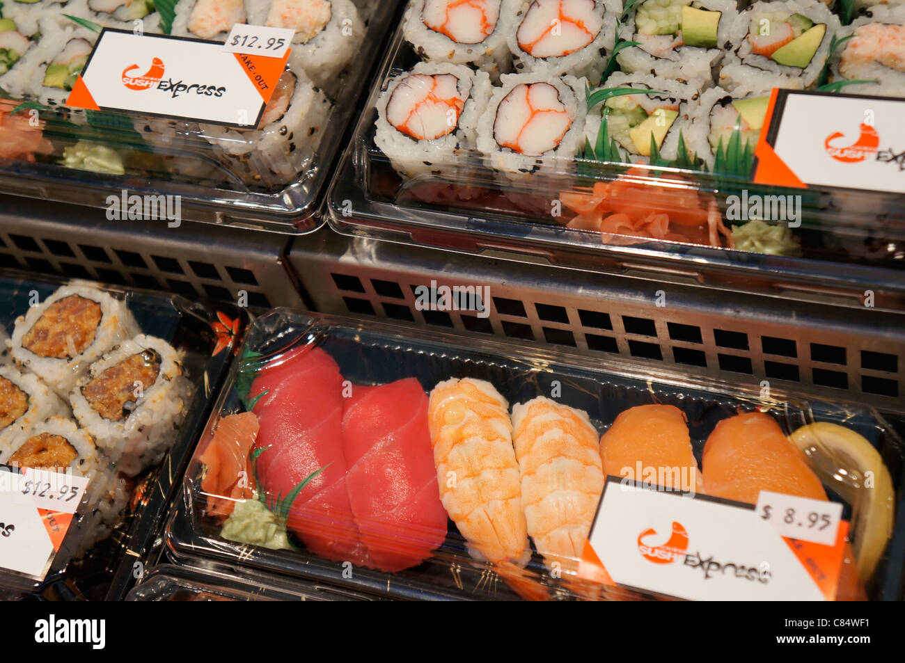 Sushi packaged in plastic containers, in fridge/freezer section - Stock Image