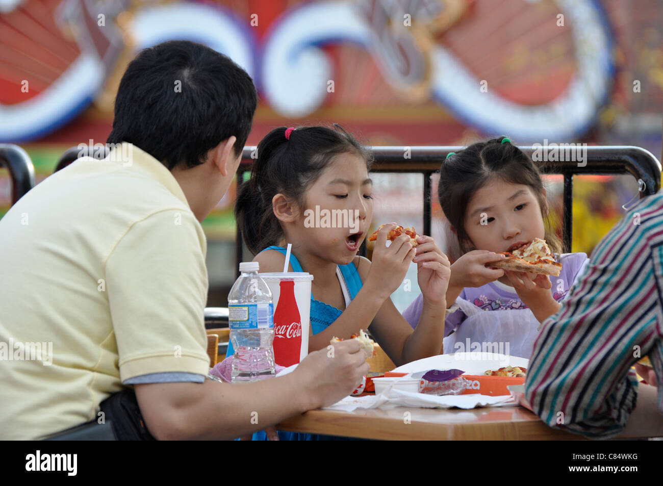 Family outdoor dining on Pizza and Soft Drinks - Stock Image