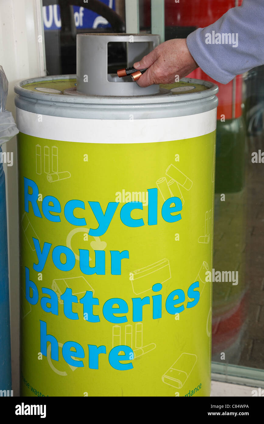England, UK, Britain. Person throwing away used batteries in a battery recycling bin. - Stock Image