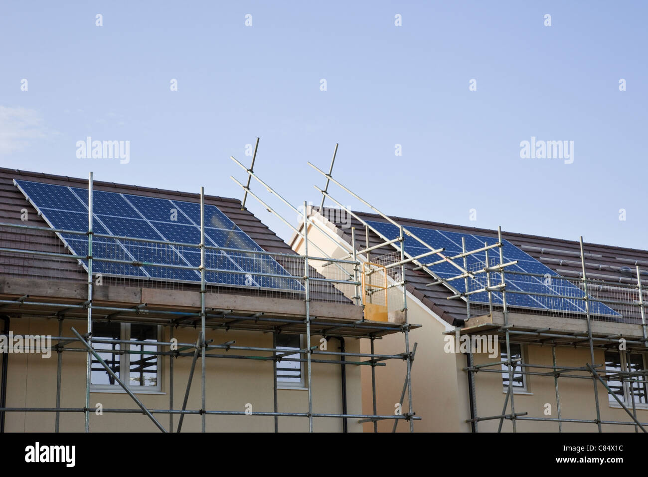 England, UK, Britain, Europe. Scaffolding for solar panels being installed on the roofs of new build houses - Stock Image