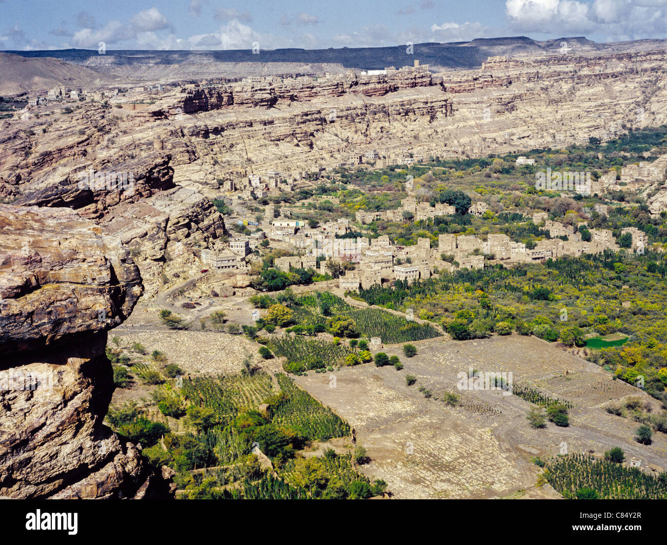 Scenic view of croplands in the valley of Wadi Dhar and hilltop village on the rim of the mountains, Yemen - Stock Image
