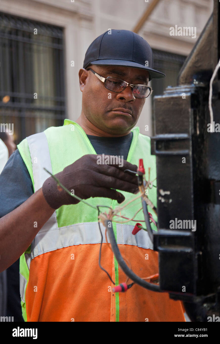 Chicago, Illinois - A worker repairs a traffic light in Chicago's financial district. - Stock Image