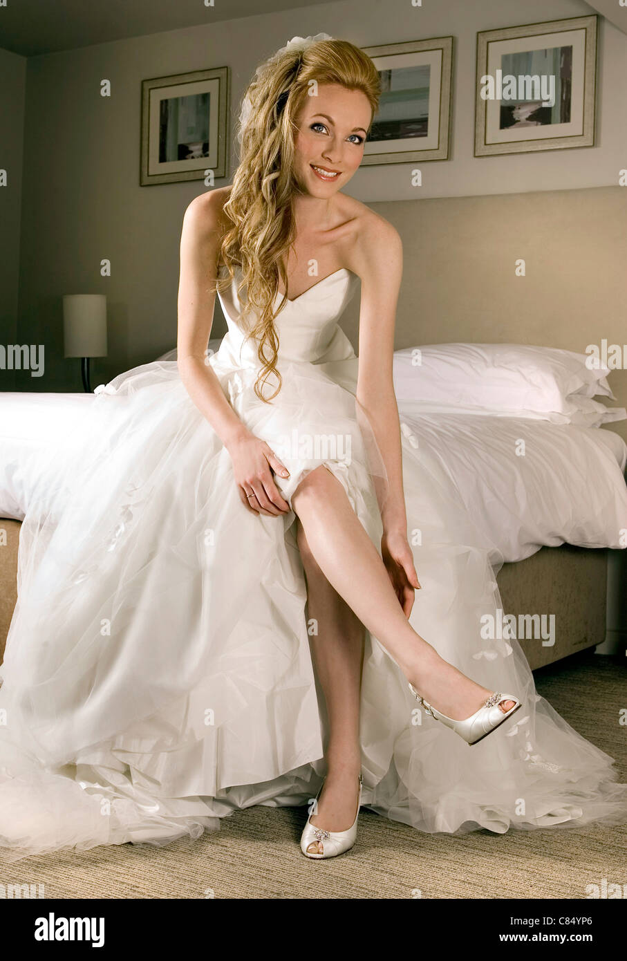 A Young Woman Posing As Bride In White Wedding Dress Putting On Pair Of Shoes Hotel Room