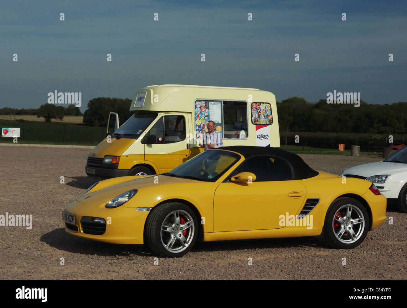 Porsche sports car in the foreground, ice cream van in the background, both in matching colours - Stock Image