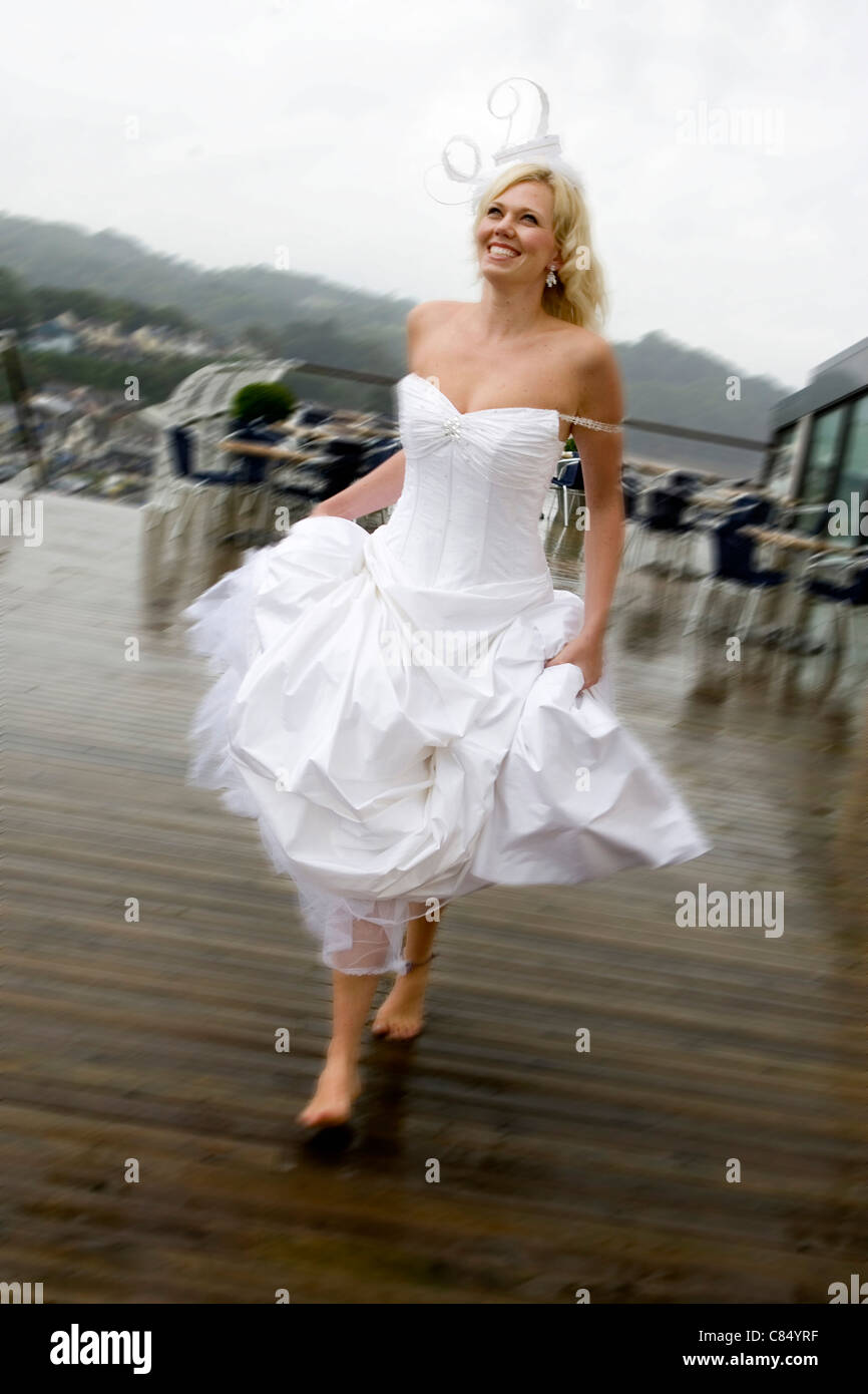 A young woman posing as a bride in a wedding dress running through a rain shower. - Stock Image