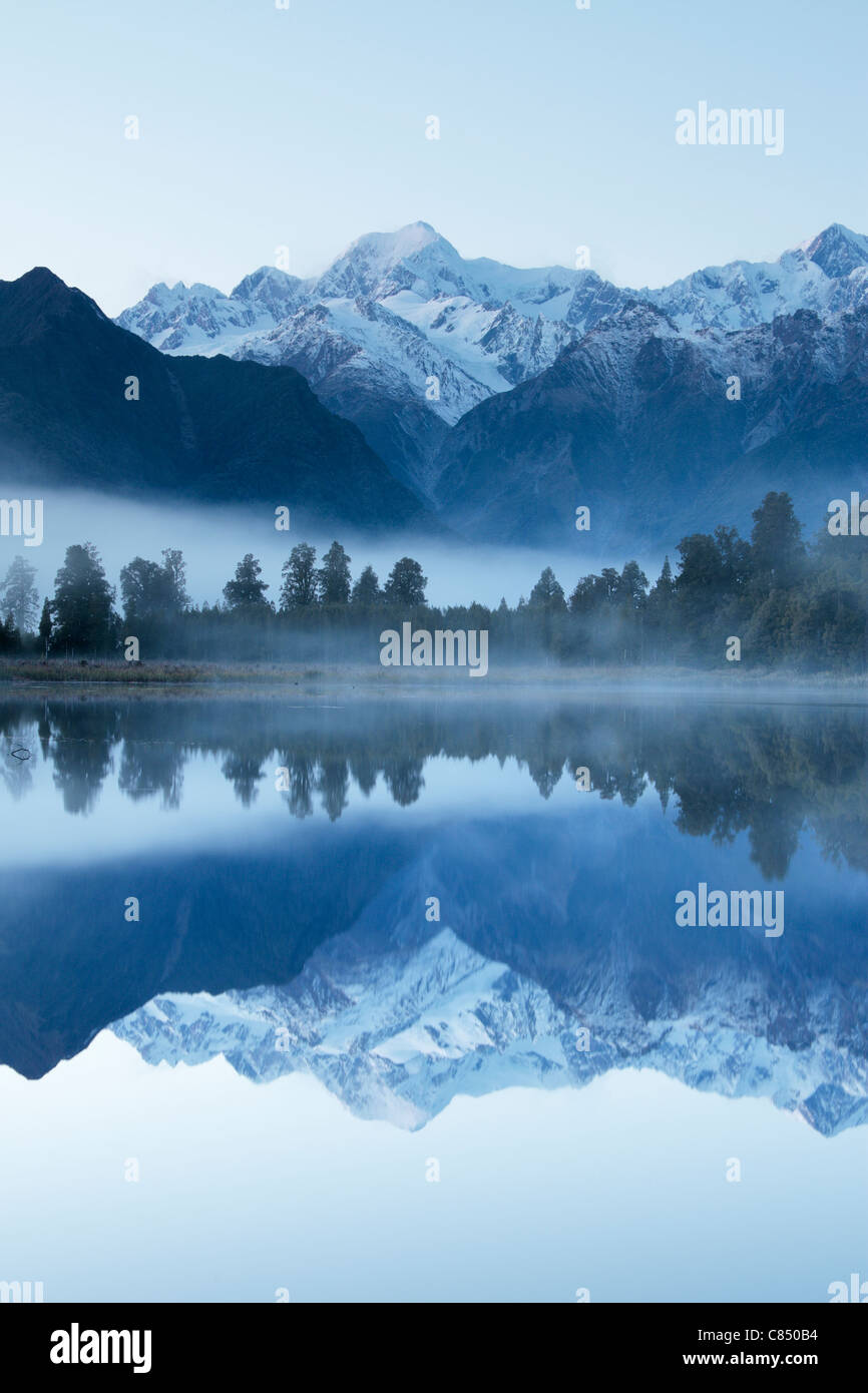 Reflection of Mt Cook (Aoraki) and Mt Tasman on Lake Matheson near Fox Glacier in New Zealand Stock Photo