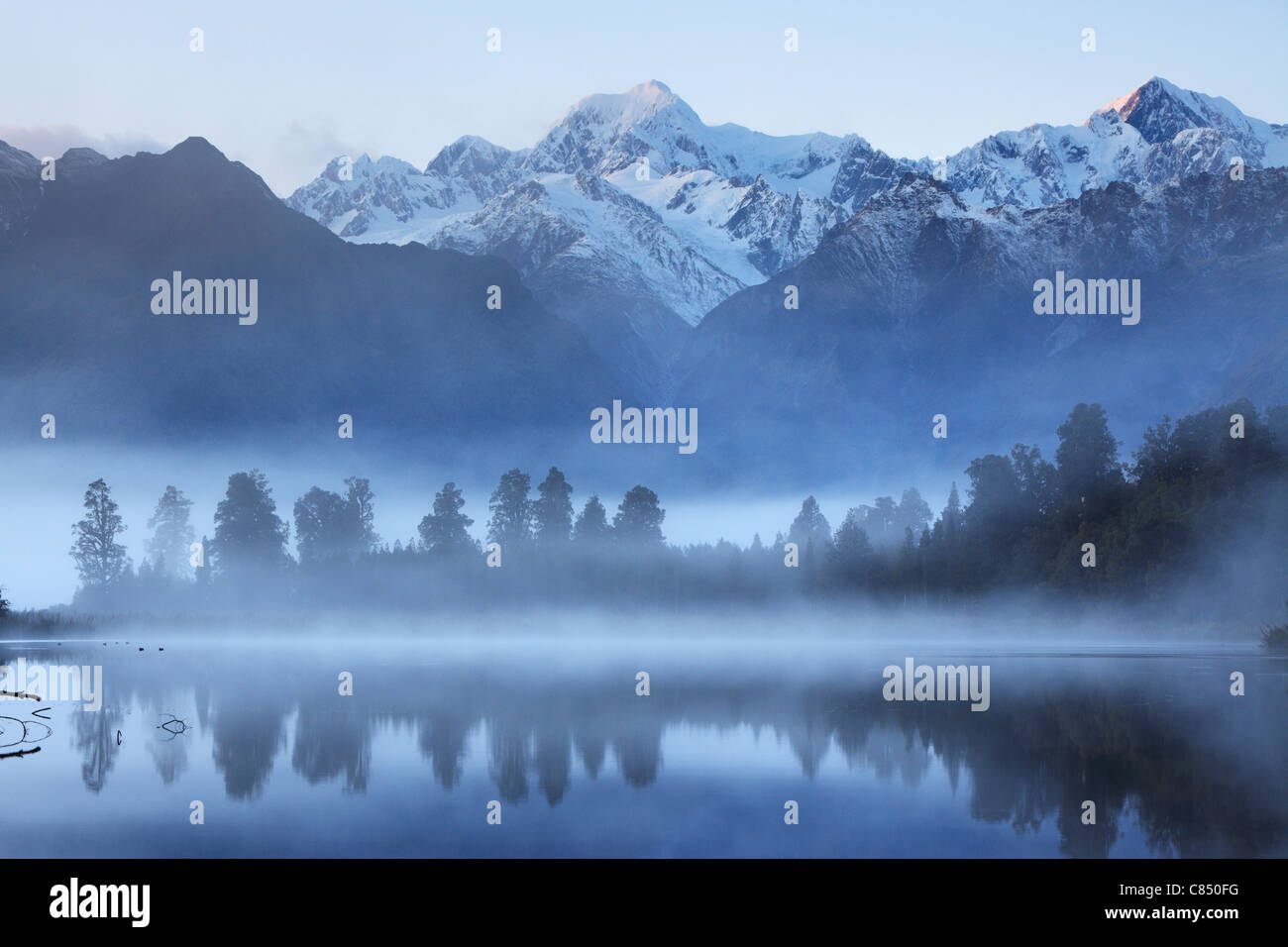 Reflection of Mt Cook (Aoraki) and Mt Tasman on Lake Matheson near Fox Glacier in New Zealand Stock Photo
