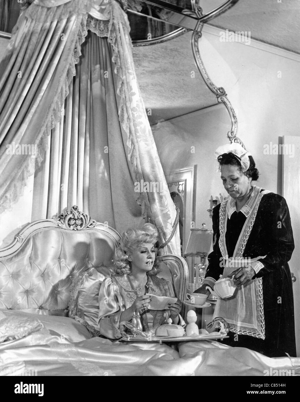 MAE WEST (1893-1980) US film actress has breakfast in bed about 1945 - Stock Image