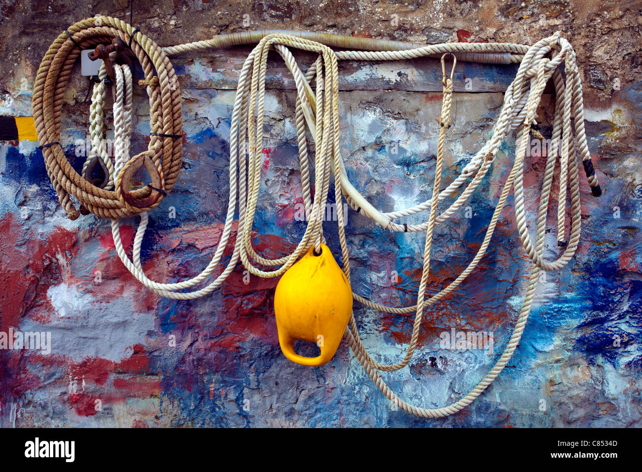 Rope and buoy hanging on a Welsh boatyard wall, splashed with various coloured paints. - Stock Image