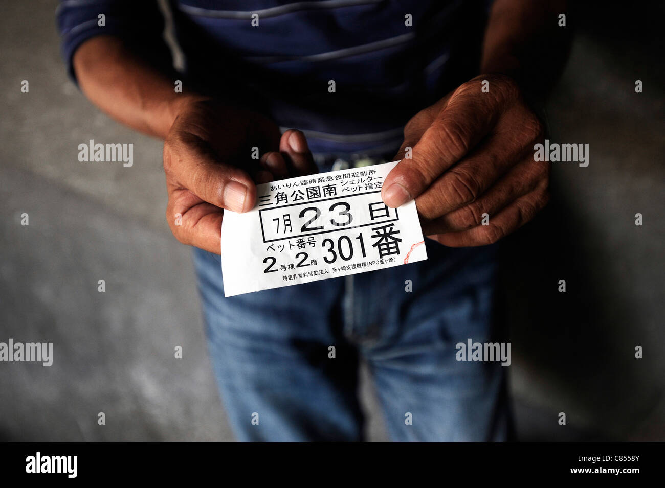 A day laborer shows the ticket he received indicating his bed number at a shelter in the Kamagasaki district of - Stock Image