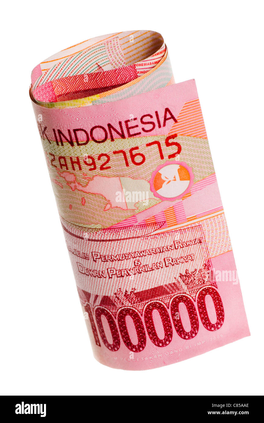 Rolled Indonesian rupiah isolated on white background - Stock Image