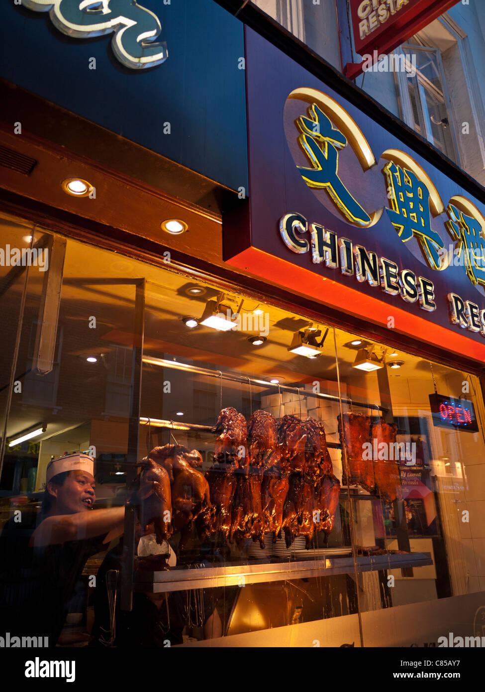 Chef arranging rows of Peking crispy duck hanging air drying in Chinese restaurant Gerrard Street Chinatown Soho - Stock Image
