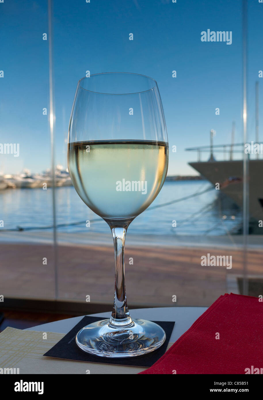 PUERTO PORTALS BAR Glass of Mallorcan white wine in waterside restaurant bar in luxury marina resort Puerto Portals - Stock Image