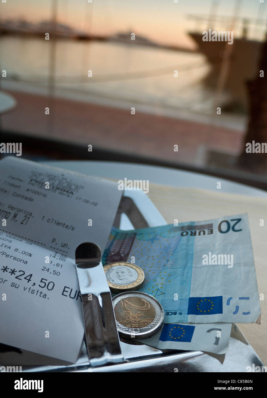 Bill with payment in Euros at luxury waterside restaurant table sunset Puerto Portals Palma de Mallorca Spain - Stock Image