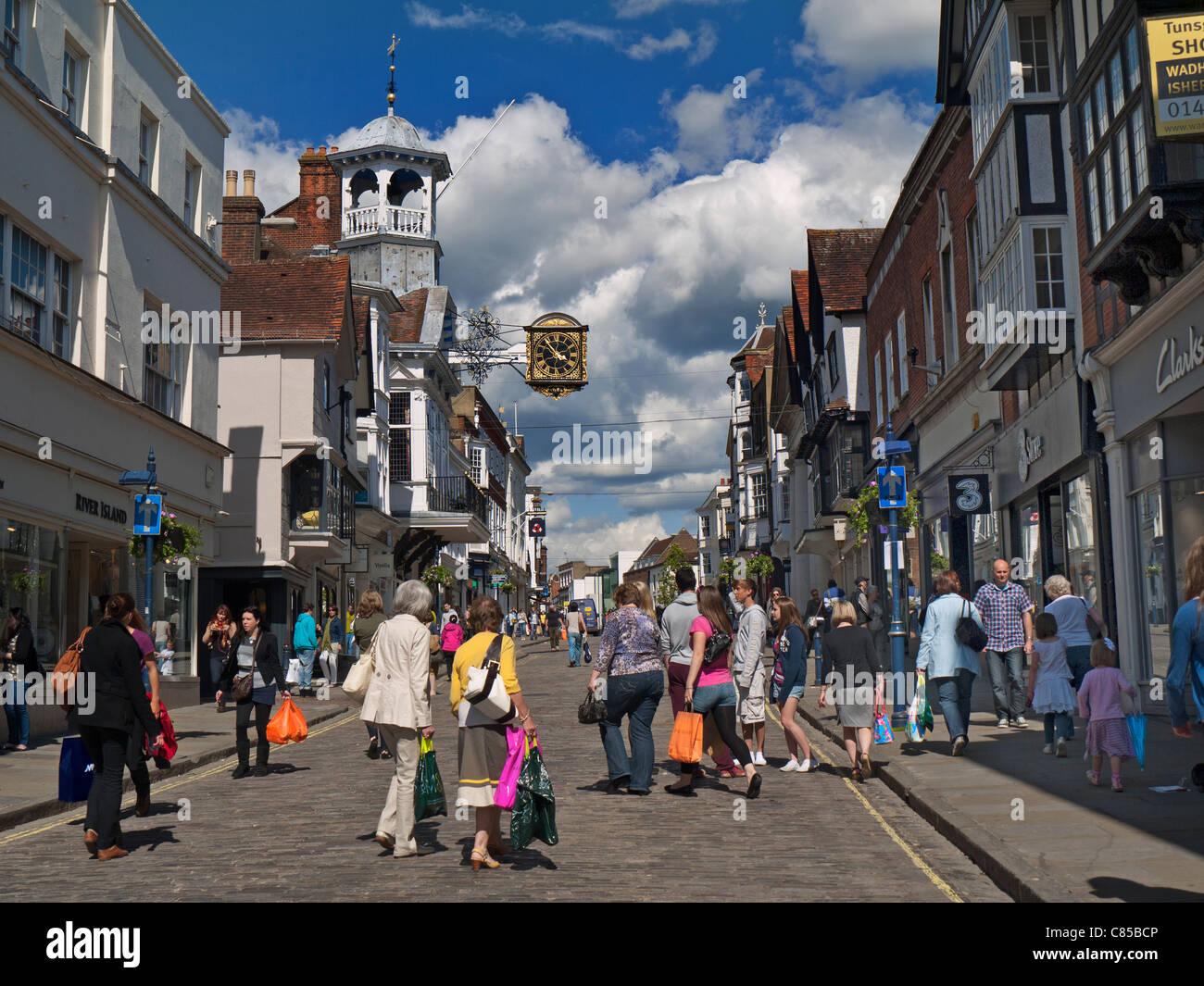 Shoppers in Guildford historic cobbled High Street enjoying spring sunshine Guildford Surrey UK - Stock Image
