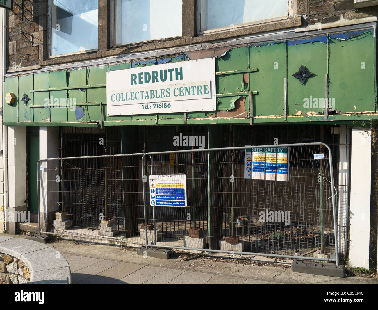 Redruth Collectables Centre closed shop with construction site barriers outside. - Stock Image