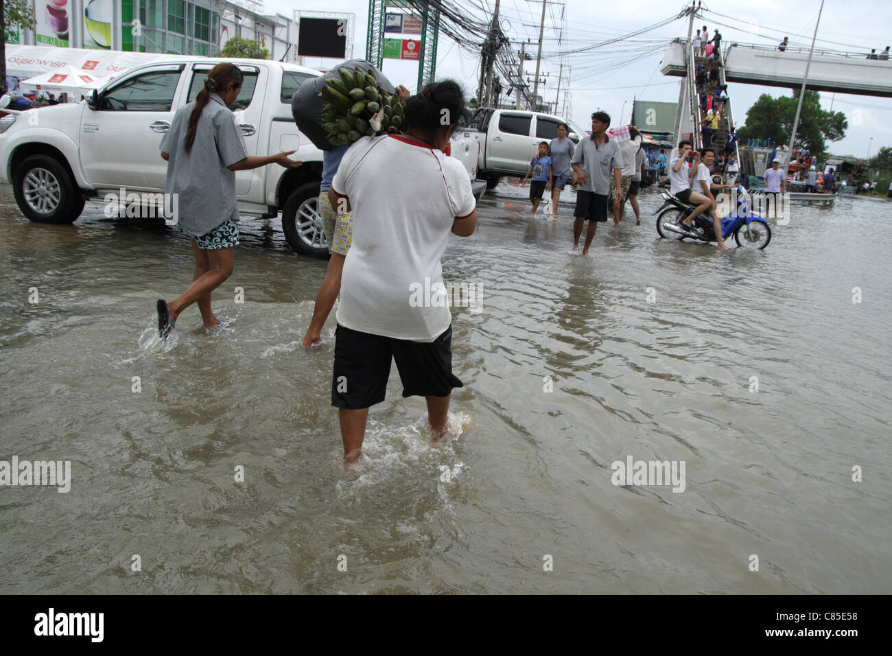 Thai people wading through floodwaters on street , Ayutthaya , Thailand Stock Photo