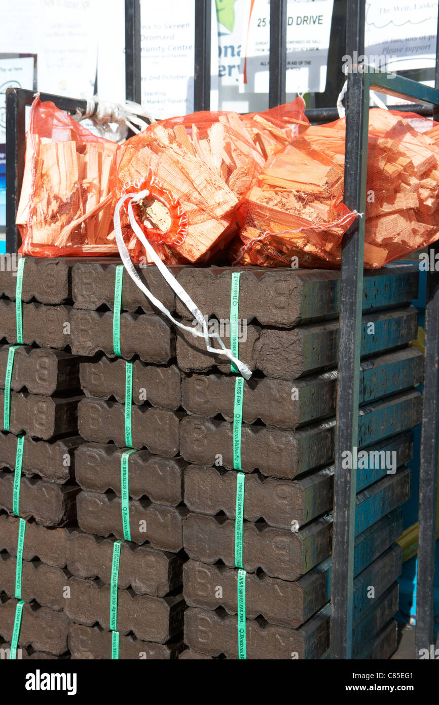 pile of bord na mona peat briquettes with sticks for sale outside a shop in the west of ireland - Stock Image