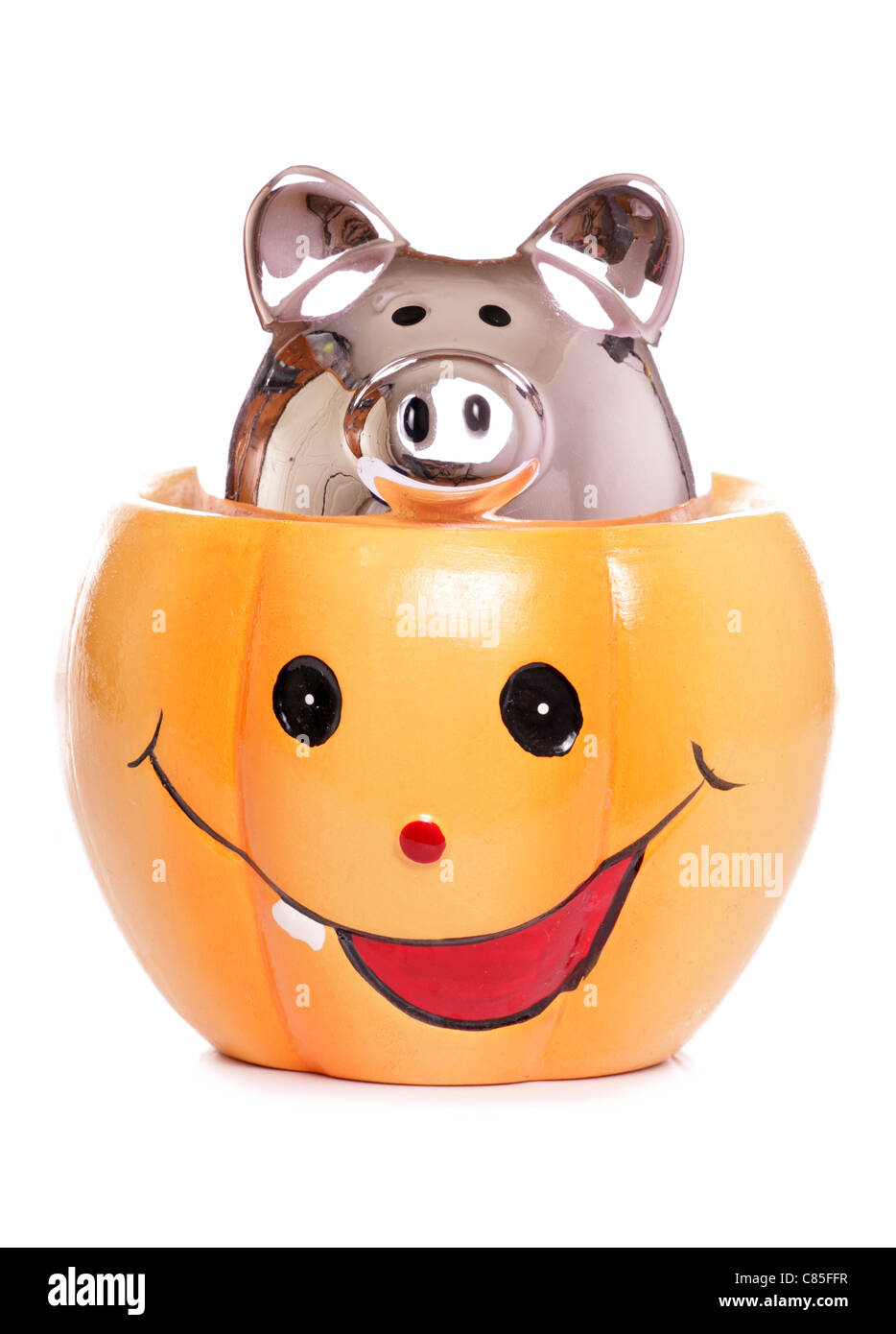 Piggybank in halloween pumpkin - Stock Image