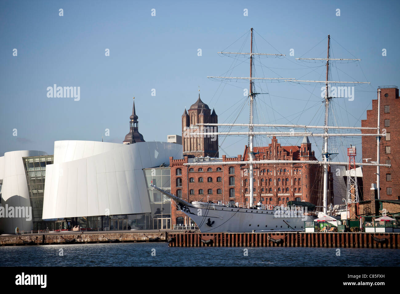 cityscape with harbor, Ozeaneum, three-mast barque Gorch Fock 1 and Saint James's Church in the Hanseatic City - Stock Image