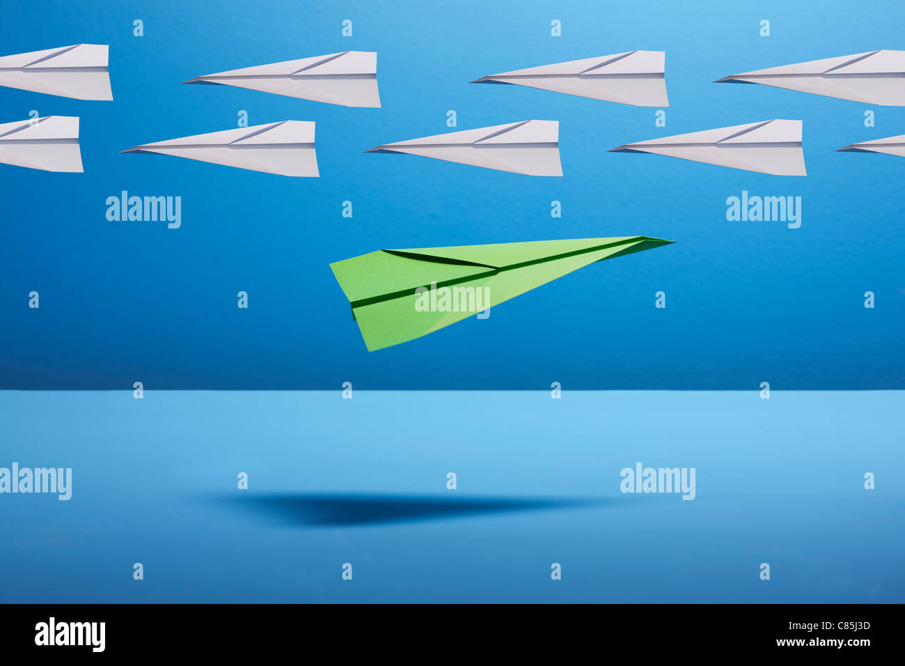 Paper aeroplanes against blue background - Stock Image