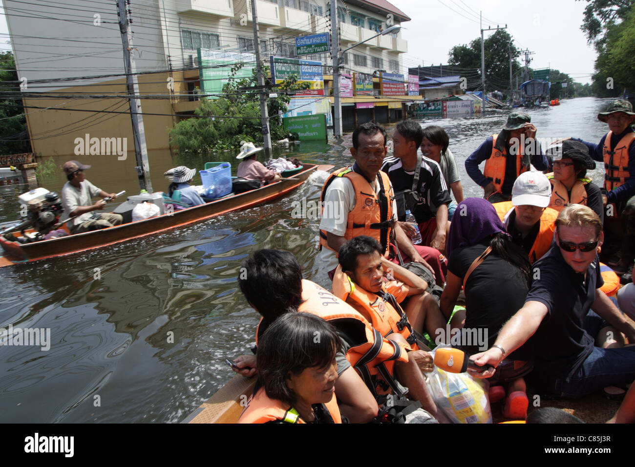 Ayutthaya residents sit in a boat as they are evacuated from their homes during floods - Stock Image