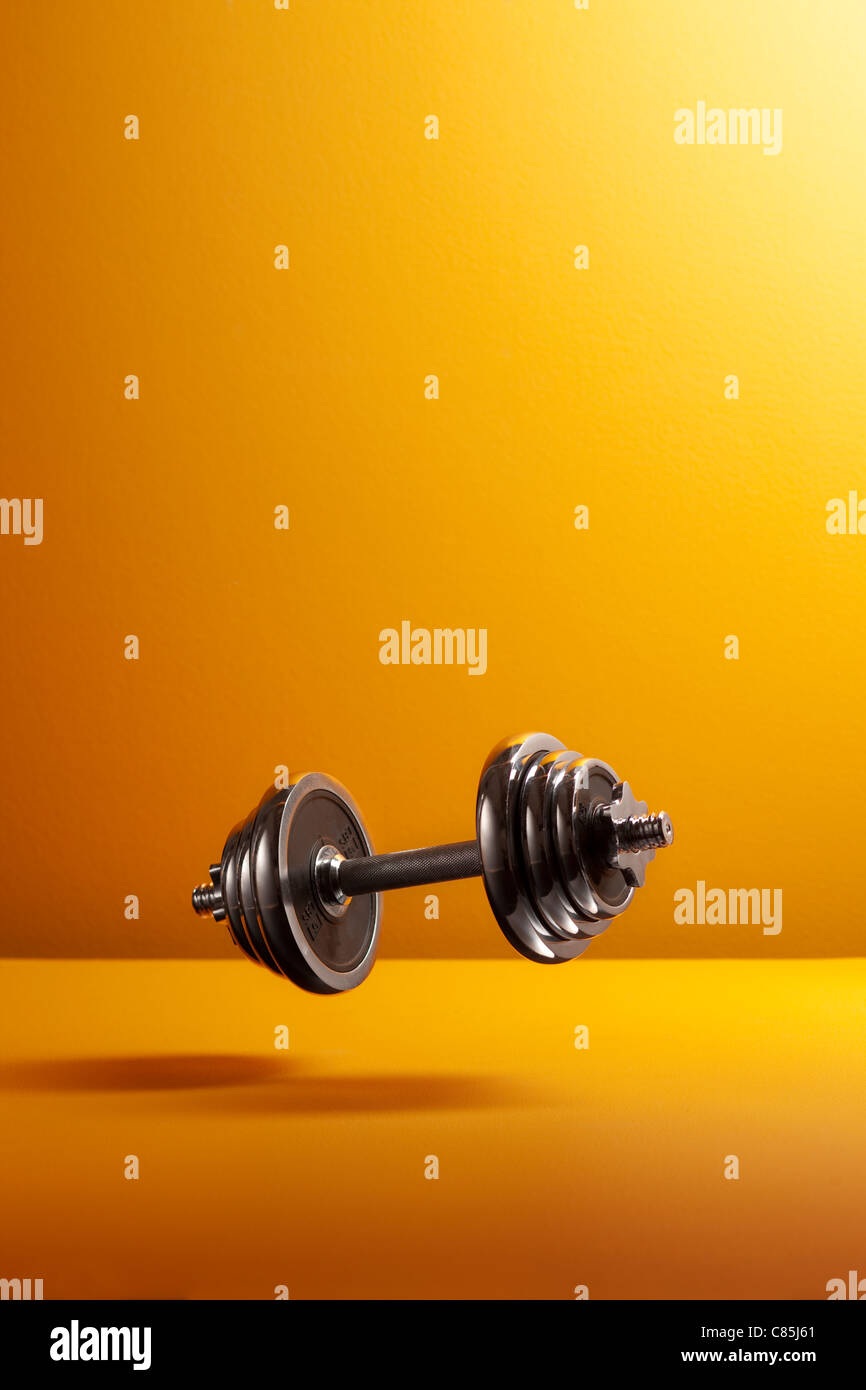 Barbells against yellow background - Stock Image