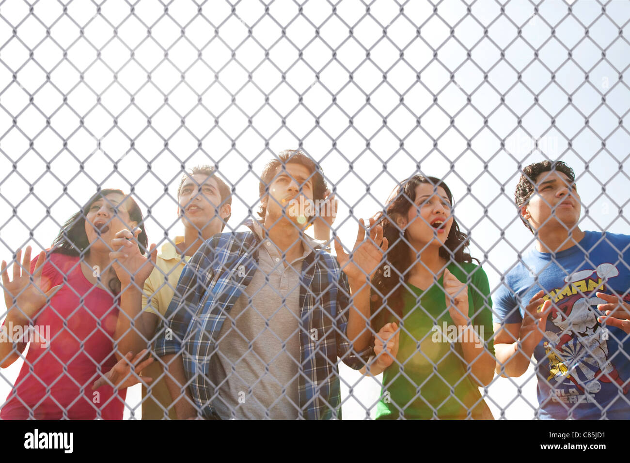Youngsters watching a match through a wire mesh Stock Photo