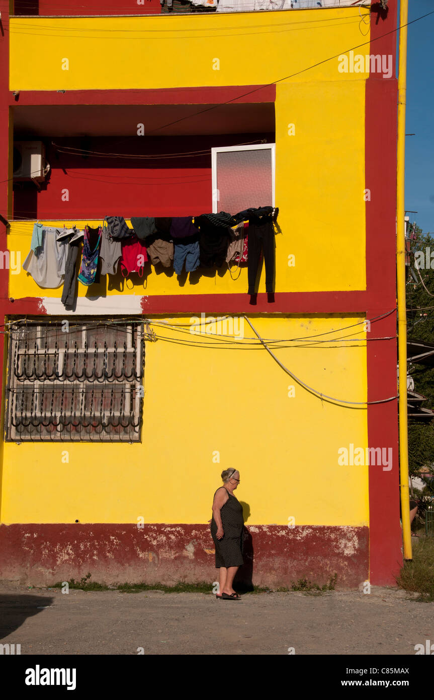Lac. Woman walking past a house painted bright yellow with washing hanging out on a hot day - Stock Image