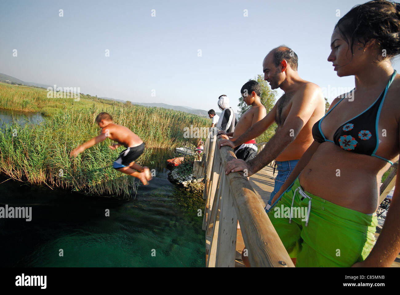 AKYAKA, TURKEY. A young boy jumping off a bridge into the Azmak river, with his family watching. 2011. - Stock Image