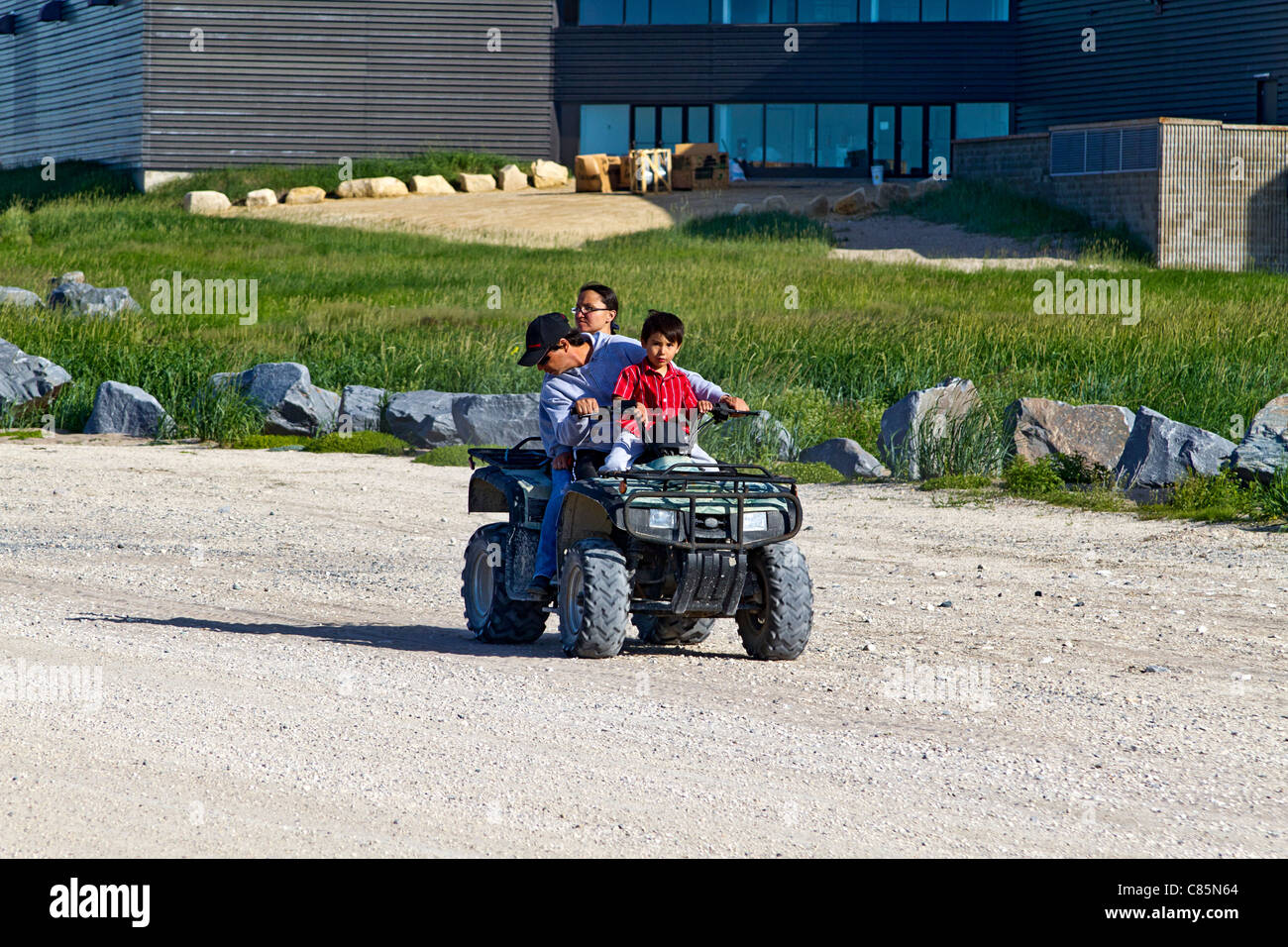 Native family (mother, father and young boy) rides a four wheel ATV around Churchill, Manitoba. - Stock Image