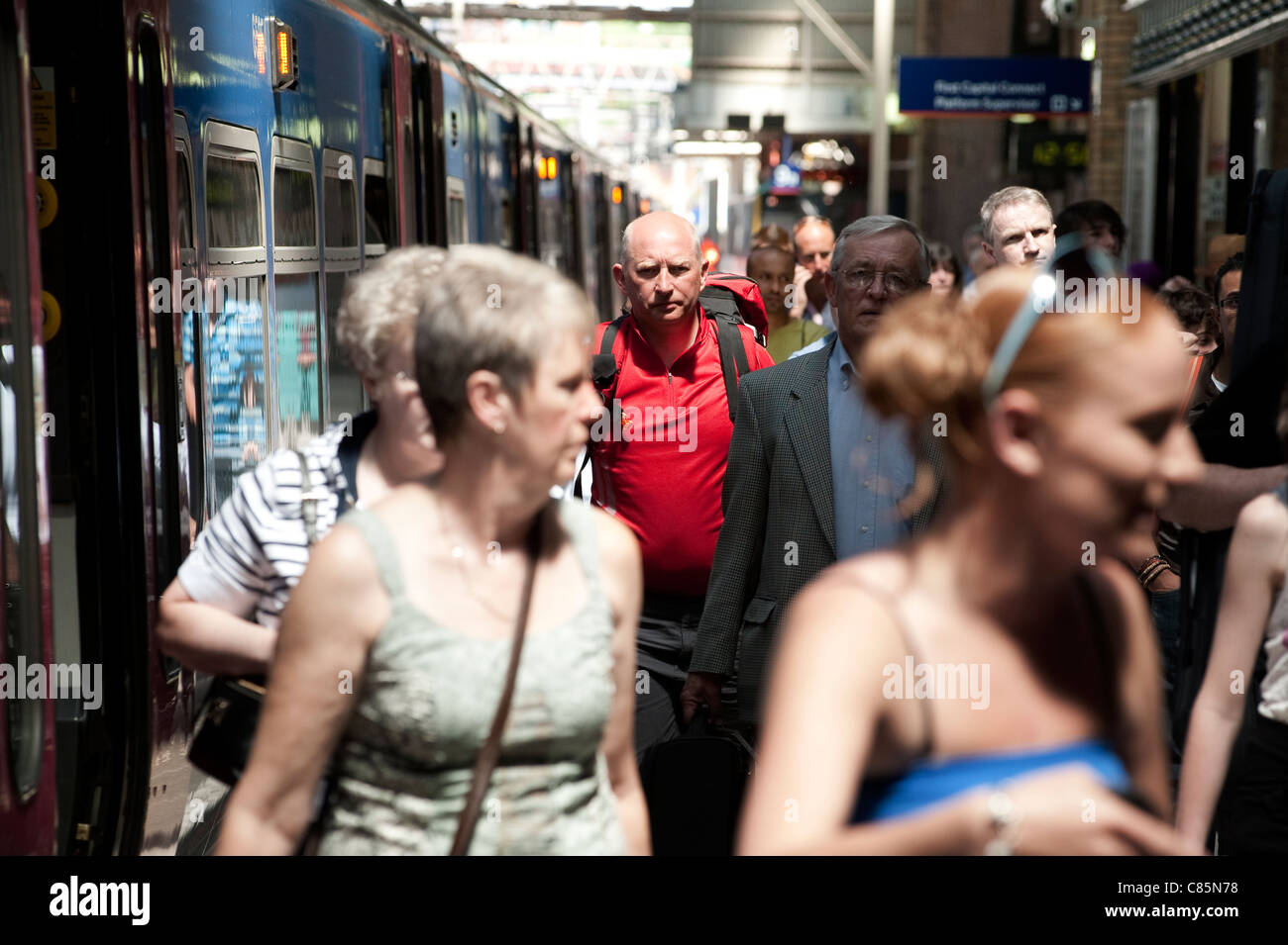 Passengers getting off of a train at a busy railway station in England. - Stock Image