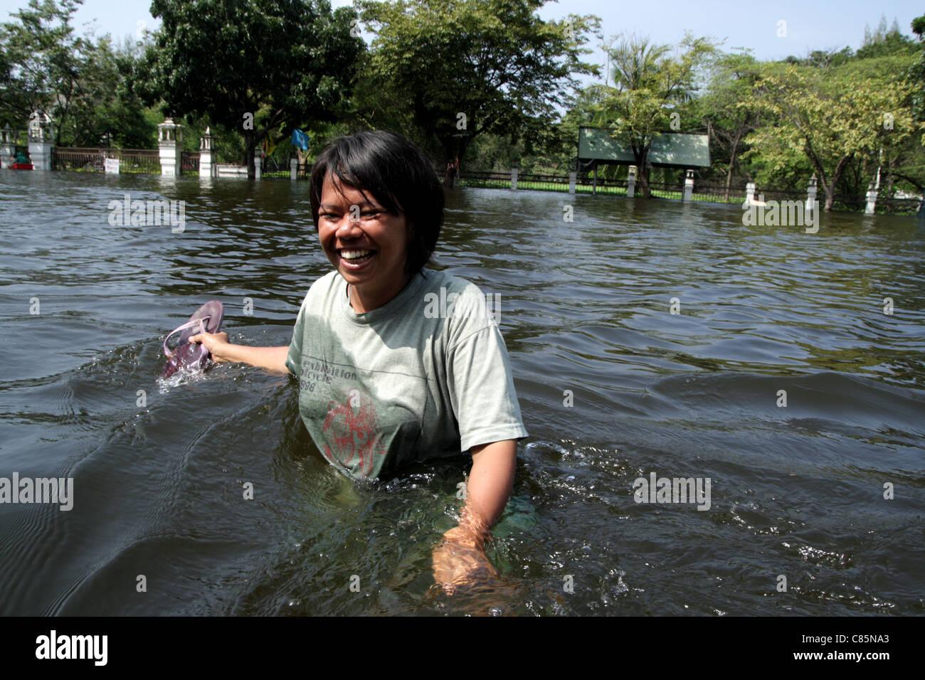 Thai people wading through floodwaters on street , Ayutthaya , Thailand - Stock Image