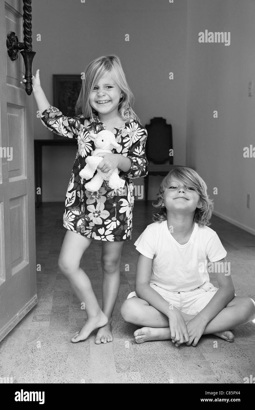 Brother and sister sitting in doorway of home - Stock Image