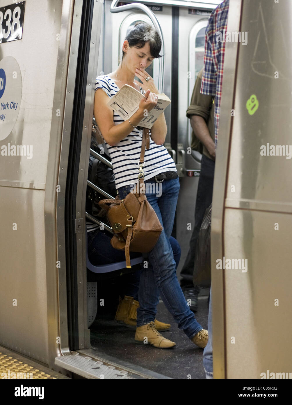 A woman is engrossed in her book while riding the subway in New York City. - Stock Image