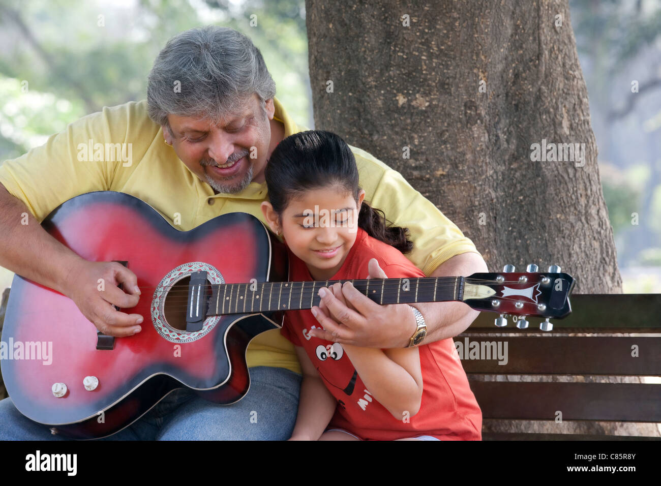 Grandfather teaching his granddaughter to play the guitar - Stock Image