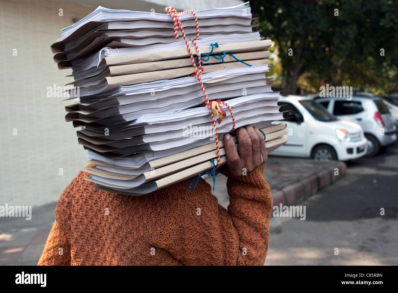 A man carries a pile of documents outside one of the courts in New Delhi, India. - Stock Image