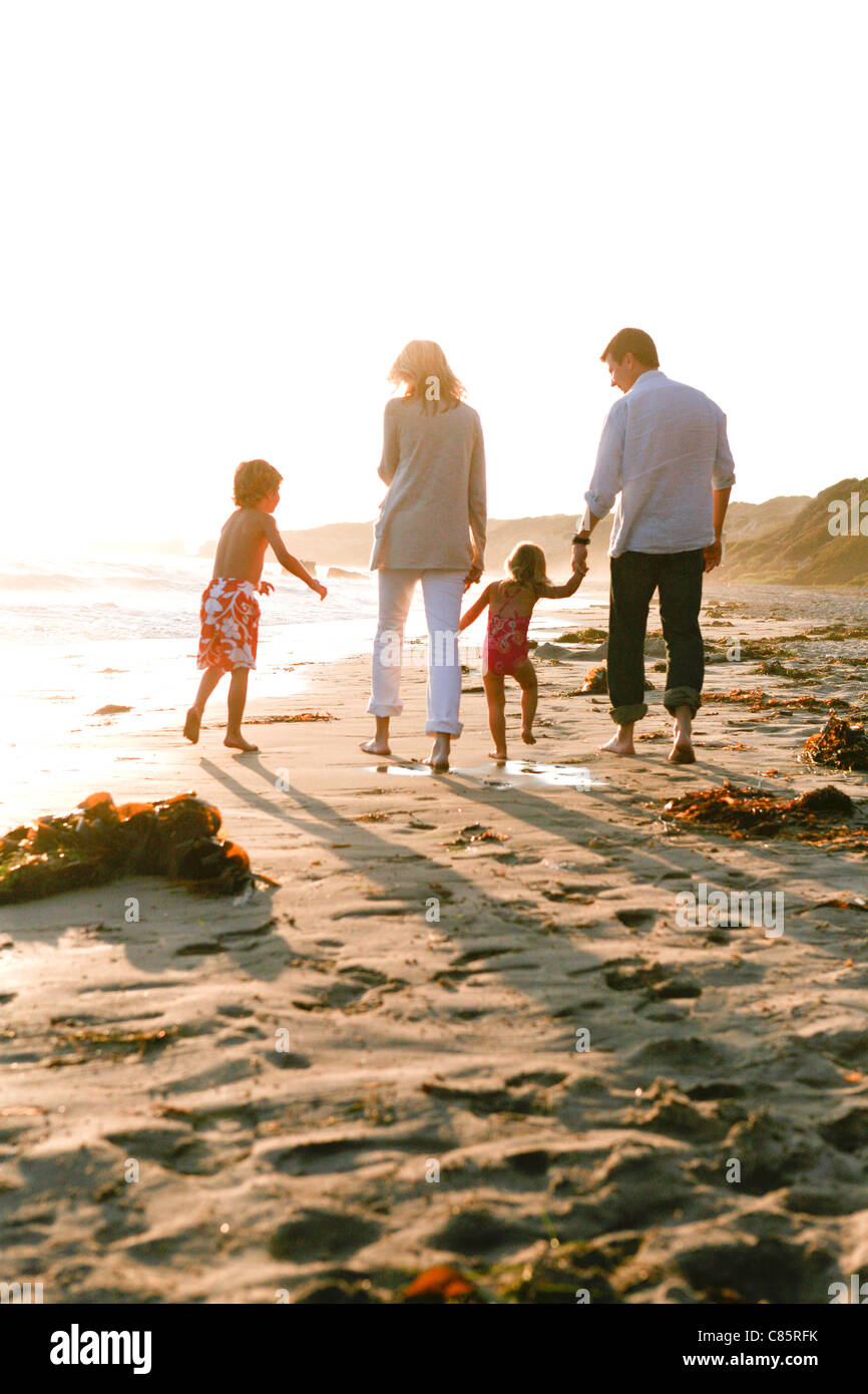 Young family walking along the beach - Stock Image