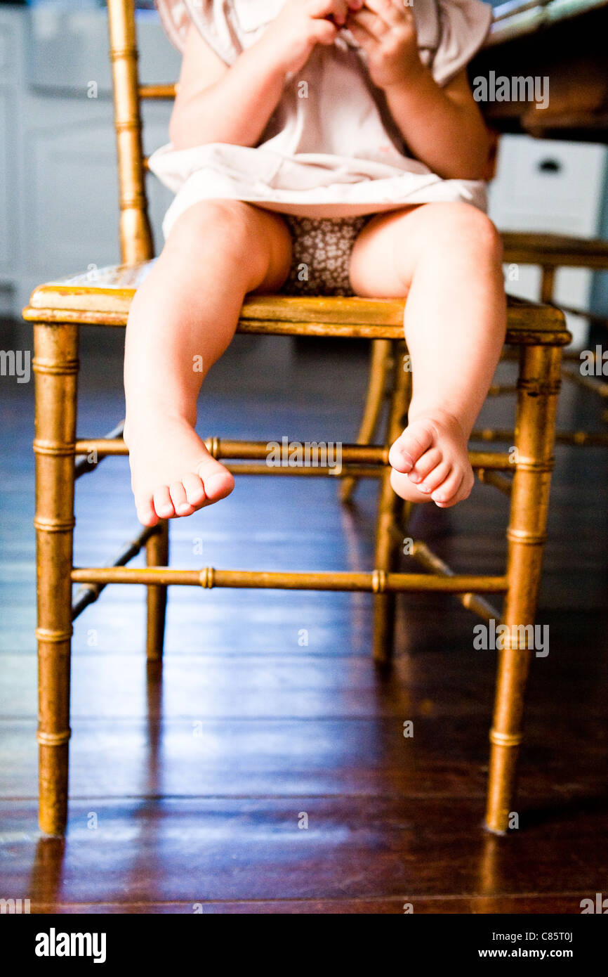 Small feet hanging off chair - Stock Image