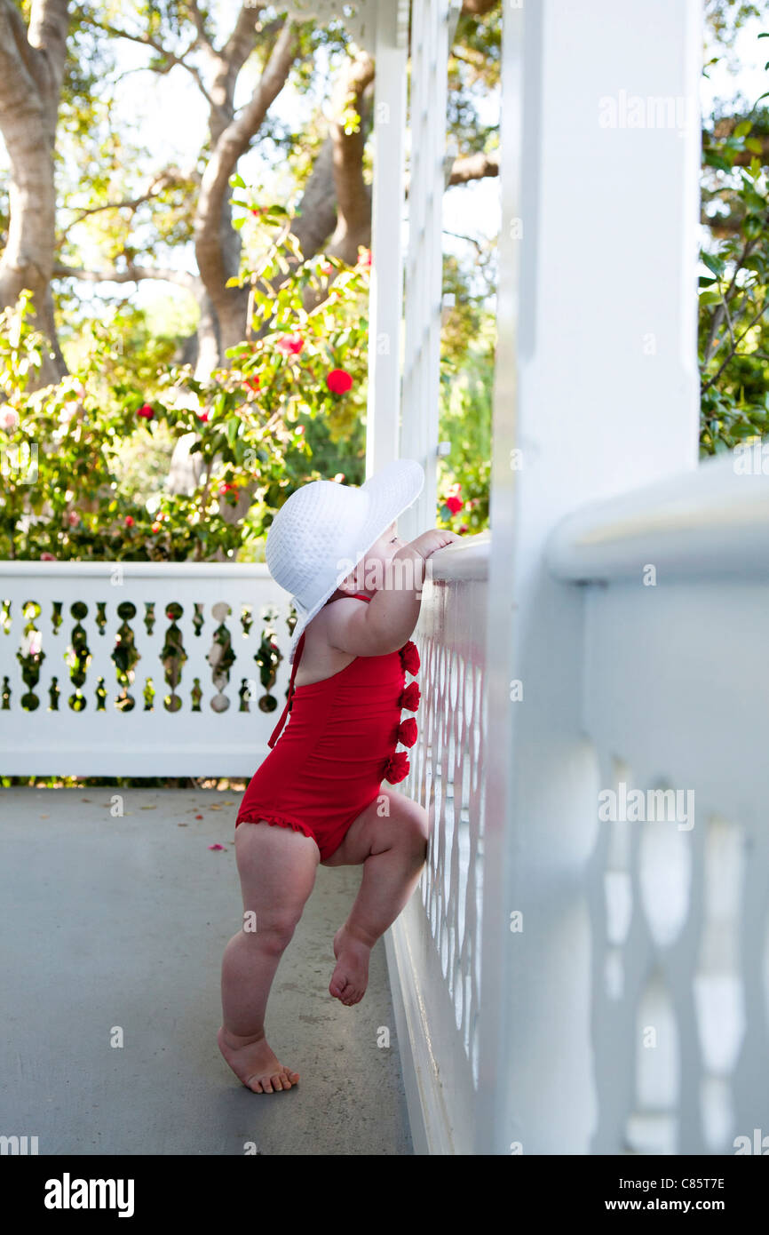 Little girl in red bathing suit on porch - Stock Image