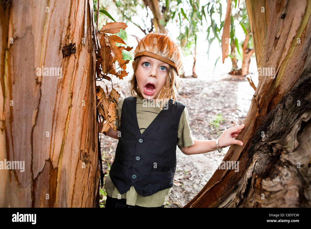 Little boy wearing a feather headdress making silly faces - Stock Image