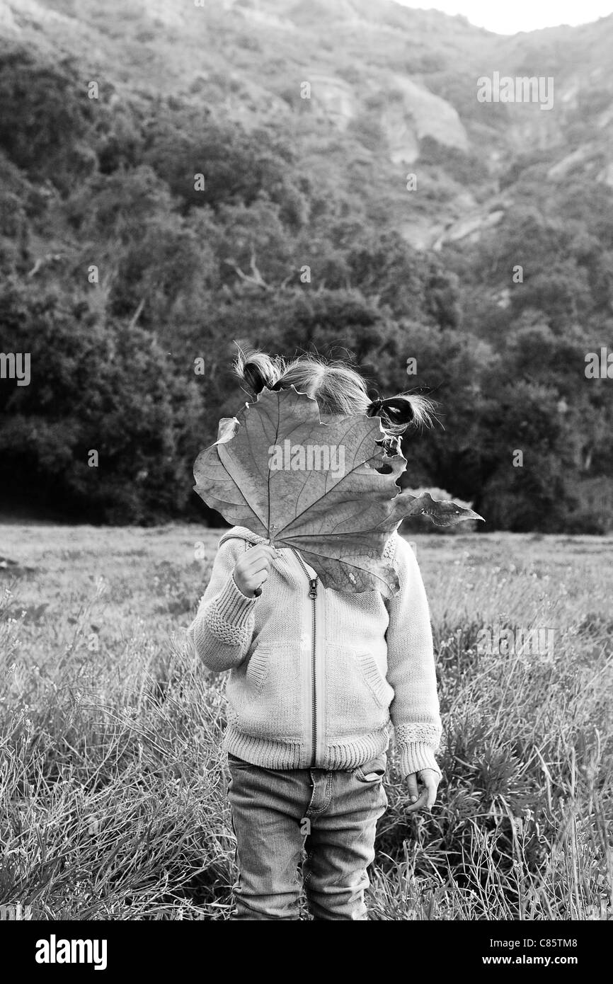 Little girl covering her face with a leaf - Stock Image