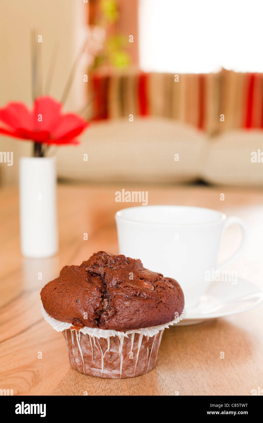 Chocolate muffin on a coffee table in a luxury home interior - Stock Image