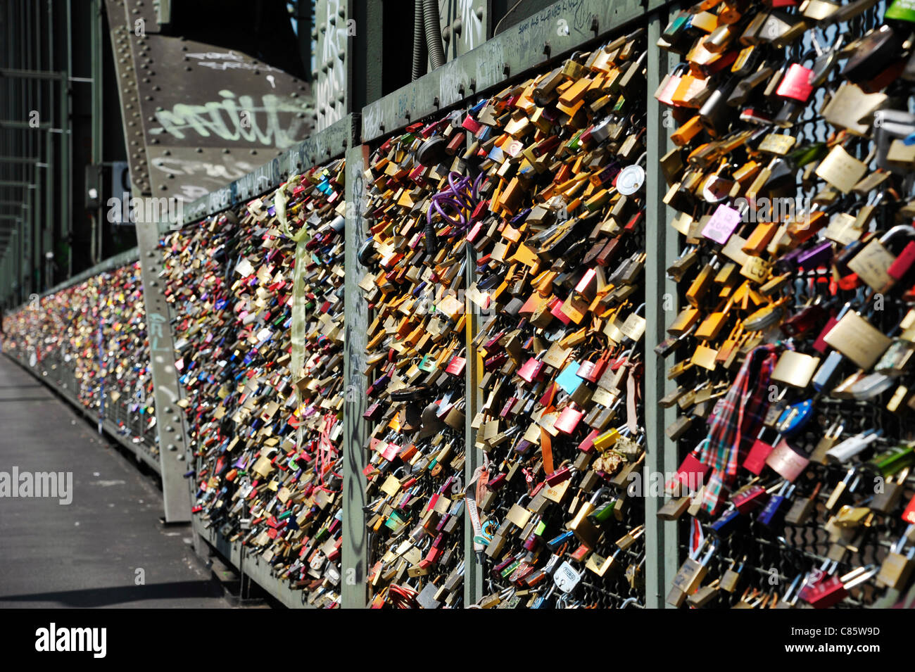 Love Padlocks, or Love Locks affixed to a security fence on Hohenzollern bridge in Cologne, Germany - Stock Image