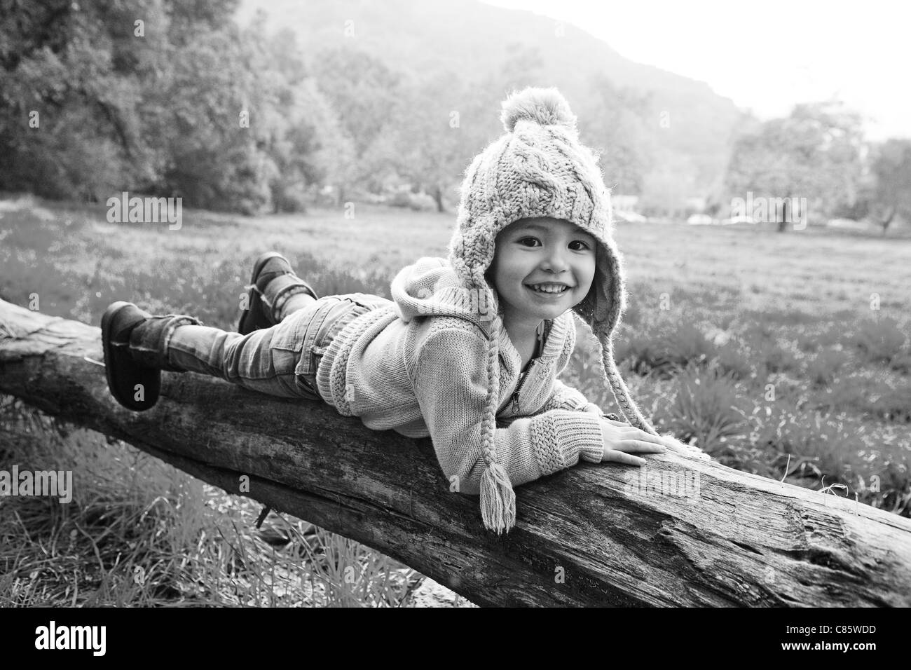 Little girl in stocking cap laying on fallen tree - Stock Image
