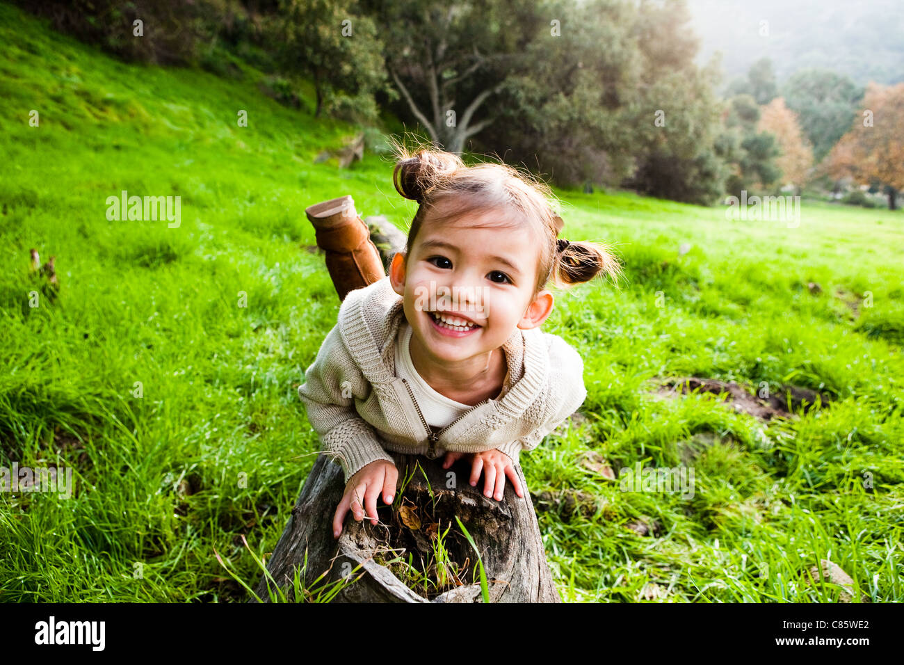 Little girl laying on fallen tree - Stock Image