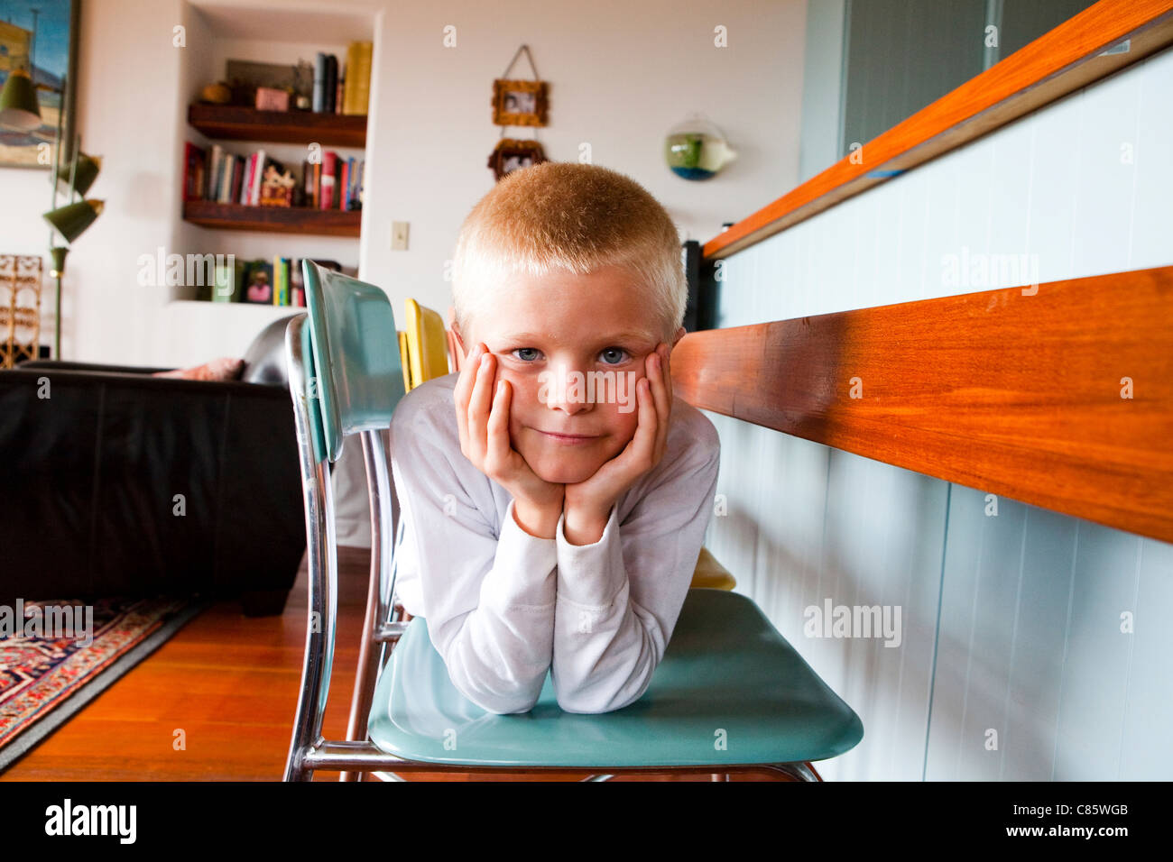 Boy laying across chairs Stock Photo