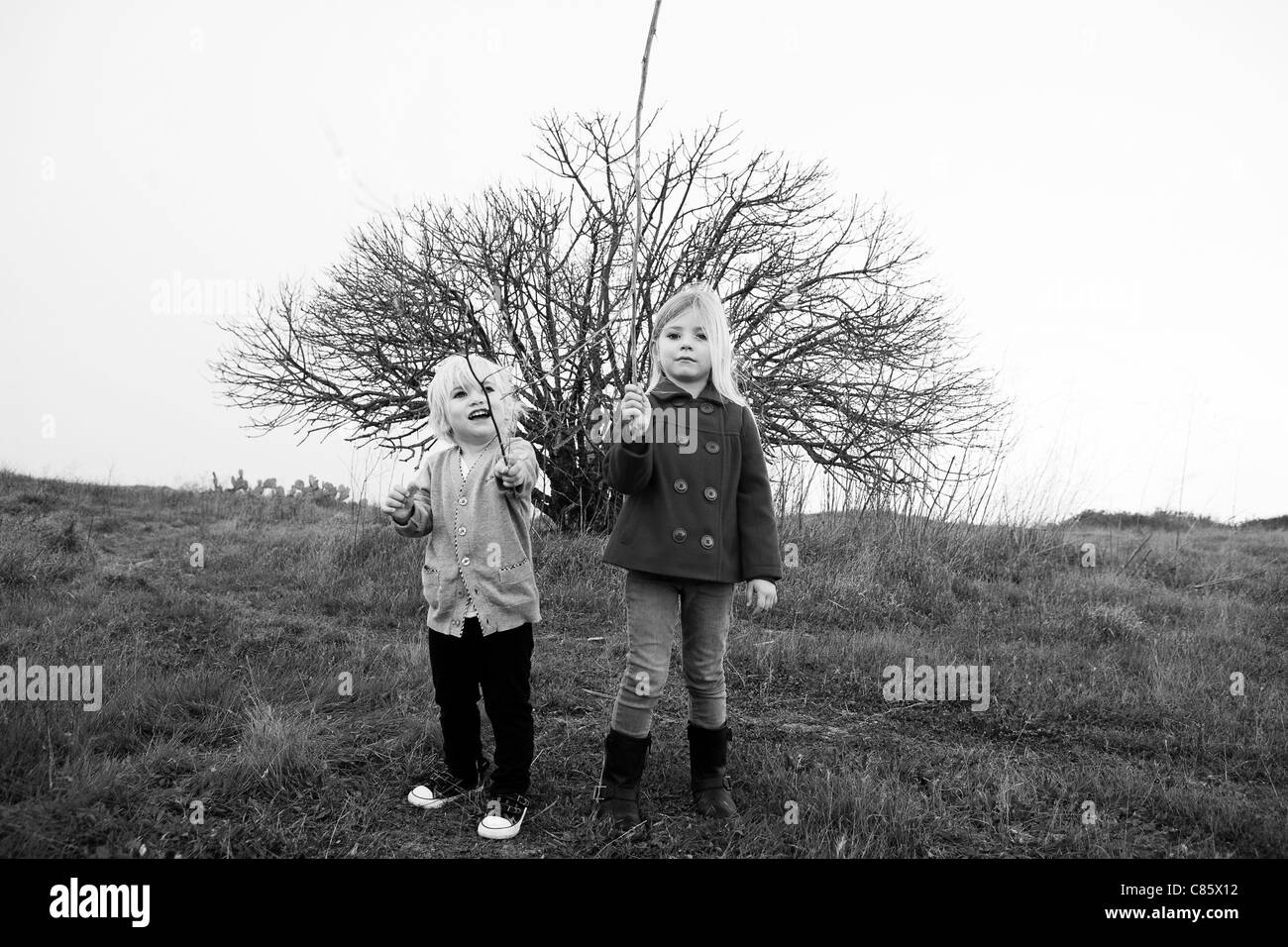Boy and girl playing with sticks - Stock Image